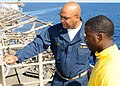 US Navy 100914-N-5538K-046 Ensign David W. Roach, left, examines the condition of electric cables with Aviation Boatswain's Mate (Handling) 3rd Cla.jpg