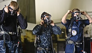 US Navy 120110-N-GC412-109 Sailors practice proper donning of self-contained breathing apparatus bottles in the hangar bay aboard the Nimitz-class.jpg