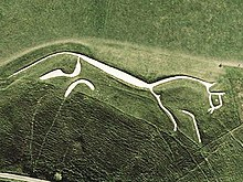 A stylised figure of a white horse cut into the hillside.
