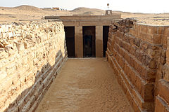 Entrance of a tomb with two columns set between long descending walls of stones.