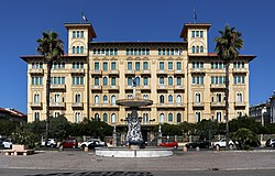 "A view of one of Viareggio's Hotel Royal along the passeggiata (""promenade""), with the ""Fountain of the Four Seasons"" by Beppe Domenici in front."