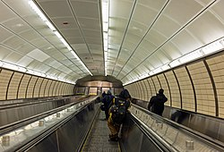 Looking down a bank of three escalators in an elliptical passage lit by fluorescent light strips above, generally white with some yellow paneling on the walls. There are several people on the escalator at varying distances from the camera
