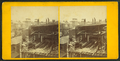 View of a house under construction, showing men finishing the chimney and building a brick wall, from Robert N. Dennis collection of stereoscopic views.png
