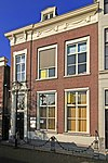 foto van Pand ter breedte van drie vensterassen onder half schilddak. Parterre en verdieping. Lijstgevel met in de architraaf gesneden ornament in late Lod. XVI-stijl