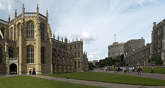 A photograph of a large Gothic chapel on the left, with tall thin windows. On the right is a line of stone buildings, pointing towards a circular tower in the middle of the picture; in the centre are two paths surrounded by grass, with a number of people walking around.