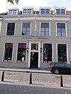 foto van Huis met gebosseerd gepleisterde gevel met kroonlijst op consoles, schuiframen en omlijste ingangspartij