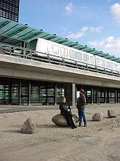 Two people look up at a train stopped at an elevated glass and concrete station