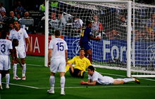 Four men in white shirts: three are standing and one is lying on the ground. A man wearing a yellow shirt is sitting on the ground. A man in a dark shirt is picking a football out of a goal.