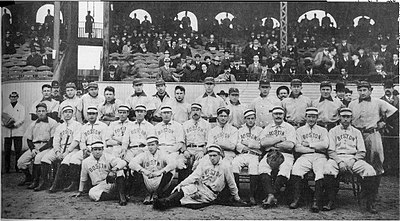 "Two rows of men in white baseball uniforms. Those in the back row wear dark baseball  caps with ""P"" on them while the men in the front row wear white hats and have ""BOSTON"" on the chest of their uniforms."