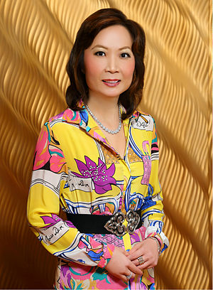 2010s in fashion - Chinese woman wearing brightly colored 1980s-inspired dress, 2013.