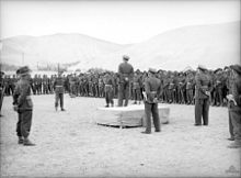 A military officer on a podium delivers a speech to gathered troops