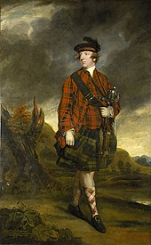 A man wearing a black hat, a red plaid shirt and socks, a green plaid kilt, and black shoes with gold buckles, carrying a satchel with its strap across his chest