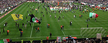 A crowd of Juventus Ultras in Curva Scirea (South) celebrates the 2012-13 scudetto with a pitch invasion.