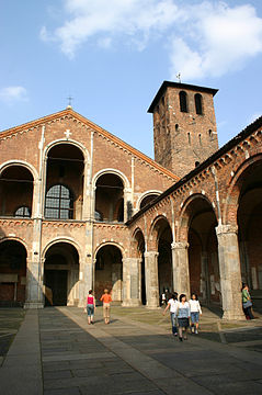 The facade and forecourt of a redbrick church are composed of simple arcades. A brick tower rises up to one side.