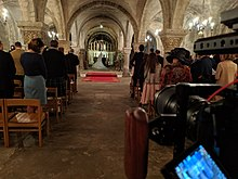A smaller DLSR camera with a rig shooting a church wedding
