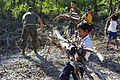 A boy at Otres Primary School in Sihanoukville, Cambodia, helps U.S. Sailors and Marines clean up the school grounds during a community service project Dec. 16, 2011 111216-N-KS651-499.jpg