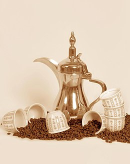 A dallah a traditional Arabic coffee pot with cups and coffee beans.jpg