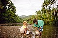A woman cleans her pots in a river while her child watches. (10664162794).jpg