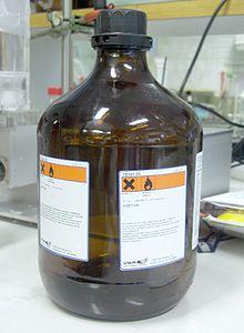 Una bottiglia in vetro ambrato di acetone, di uso comune in un laboratorio chimico.
