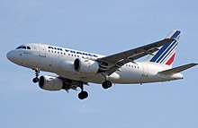 White jet aircraft coming into land, undercarriage fully extended. Under each wing is a turbofan engine