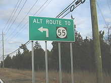 A green sign along a road lined with trees and power lines reading alt route to Route 55 with an arrow pointing to the left