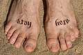 Ambigram tattoo Stay here written on feet.jpg