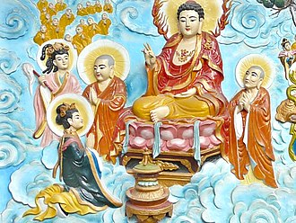 Religion in Vietnam - Amitabha Buddha, the master of the Pure Land, blesses a female devotee in this relief at Quan Am Pagoda, Cholon.