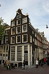 foto van Hoekhuis ten dele gerestaureerd, ten dele herbouwd met gevel op houten pui, bekroond door een klokvormige top