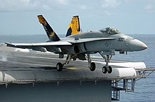 F/A-18 Hornet fighter departing aircraft carrier. A gray aircraft, with blue and yellow fins, has just left the edge of carrier's deck, as evident through the extended landing gear.