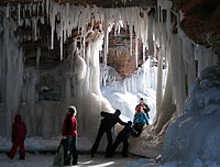 People climbing into a frozen sea cave with large icicles