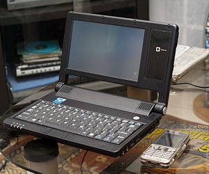 NanoBook - An Astone UMPC with a mobile phone beside it to provide scale.