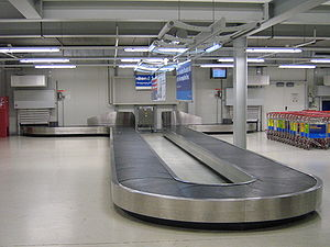 Baggage carousel - A single level baggage carousel at Frankfurt-Hahn Airport.  The baggage comes out through one of the holes in the walls and goes back in to circulate around the circle again.