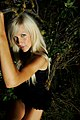 Blonde woman with black clothing next to vegetation.jpg