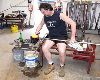 Glassblowing - A stage in the manufacture of a Bristol blue glass ship's decanter. The blowpipe is being held in the glassblower's left hand. The glass is glowing yellow.