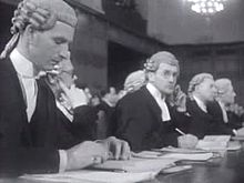Six members of the British legal team seated at a table.