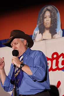 Man onstage in a Stetson hat in front of a picture of Oprah Winfrey