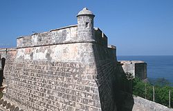 The top of a wall that appears to belong to an old castle. The sea is visible in the distance.