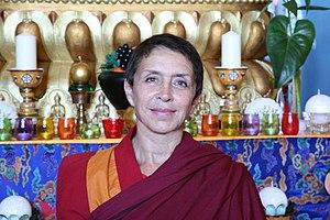 Davina Delor - Davina Delor in front of her Buddhist religious symbols
