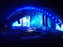 The Viva la Vida Tour visited arenas and stadiums in separate phases of the tour. In London, the band visited The O2 Arena in 2008 (left), and Wembley Stadium in 2009 (right), with the latter show featuring a half-dome stage design.