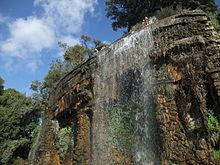 Vue de trois-quarts d'une cascade de quelques mètres de hauteur et de largeur dans un parc sous un ciel bleu.