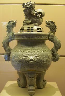 Một chiếc đỉnh bằng gốm tráng men trang trí đắp nổi rồng và nghê do thợ làng Bát Tràng chế tạo vào năm 1736, thời Cảnh Hưng.