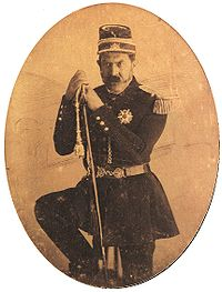 Three-quarters length tintype portrait showing a mustachioed man in military dress uniform and cap with one foot resting on a rock and holding a sheathed sword.