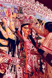 Woman placing red pigment on the forehead of a many-armed goddess