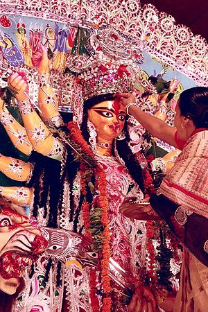 Worship in Hinduism - Sindoor being applied on the forehead of Goddess Durga during Durga Puja.