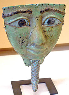 An oversized, shallow mask depicting a large face. The face is roughly oval-shaped, but the top of the mask is a horizontal line just above the eyebrows, leaving the entire mask roughly triangular. The entire face is flattened, but the bulbous nose protrudes away from the face. The eyes are large and almond shaped, and both the eyes and braided eyebrows are disproportionally large in comparison with the mouth, which has full lips. The front of the face is clean-shaven, but below the chin, there is a long, narrow, pointed, braided false beard that was characteristic of ancient Egyptian royalty.
