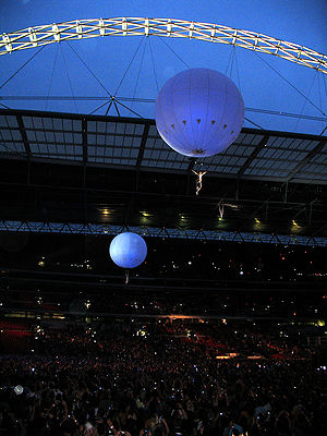 Black Holes and Revelations - Acrobats suspended from giant white balloons float above the audience in the first, sellout night of Muse's Wembley gigs