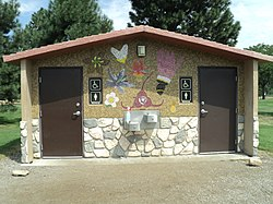 A picture outside of a public toilet in a recreational area with public art. There are separate units for males and females, which are handicap accessible. There are drinking fountains provided on the outside.