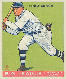 A baseball card image of a man in a white baseball uniform and blue baseball cap swinging a baseball bat