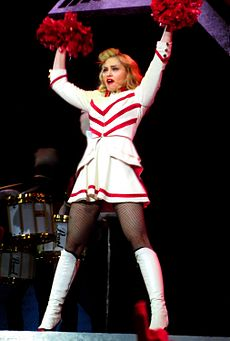 A blond woman standing on a stage wearing a drum major's dress in white and red and long white boots. She has raised her arms above and shakes a pair of pompoms.