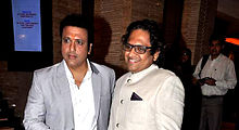 A serious Govinda with a smiling man